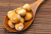 Hazelnuts on a wooden spoon on a bamboo mat — Stock Photo