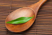 Green leaf on the wooden spoon on a bamboo mat — Stock Photo