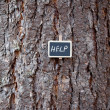 Background of tree bark and blackboard with the inscription help — Lizenzfreies Foto