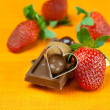Chocolate bars, strawberry, heart and the candy on the orange fa — Stock Photo