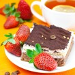 Stock Photo: Lemon tea, cake and strawberries lying on orange fabric