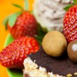 Cake, chocolates and the strawberries on the orange fabric — Stock Photo