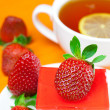 Lemon tea, cake and strawberries lying on the orange fabric — Stock Photo #6119033