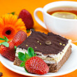 Gerbera, lemon tea, cake and strawberries lying on the orange fa — Stockfoto