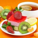 Lemon tea, kiwi,cake and strawberries lying on the orange fabric — Stock Photo
