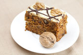 Piece of cake with nuts lying on the plate — Stock Photo