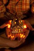 Decoratieve huis met een kaars in de handen van de mens — Foto de Stock