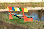 Multi-colored bench standing in a park near the pond — Stock Photo