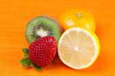 Kiwi,lemon,mandarin and strawberries lying on the orange fabric — Stock Photo
