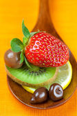 Strawberries, kiwi and chocolate candy in the wooden spoon of th — Stock Photo