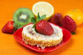 Cake,kiwi,lemon,mandarin and strawberries lying on the orange fa — Zdjęcie stockowe