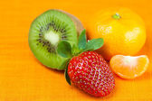 Kiwi,mandarin and strawberries lying on the orange fabric — Stock Photo