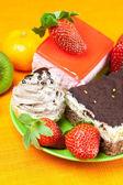Mandarijn, kiwi, taart en aardbeien liggend op het oranje weefsel — Stockfoto