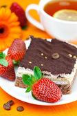 Gerbera, lemon tea, cake and strawberries lying on the orange fa — Stock Photo