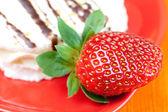 Cake and strawberries lying on the orange fabric — Stock Photo