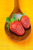 Strawberries in wooden spoon of the orange fabric — Stock Photo