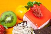 マンダリン、キウイ、ケーキ、イチゴ、オレンジ色の布の上に横たわる — ストック写真