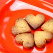 Cookie in the form of heart in a plate on a red background — Stock Photo #6123474