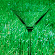 Conceptually illuminated martini glass on a background of green — Stock Photo