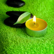 Burning candle and spa black stones lying on the towel - Lizenzfreies Foto