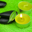 Burning candle and spa black stones lying on the towel - Foto Stock