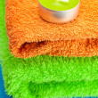 Background of the three multi colored terry towels and candle - Zdjęcie stockowe