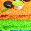 Background of the three multi-colored bath towels, black spa sto — Stock Photo
