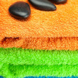 Background of the three multi-colored terry towels and spa black - Foto Stock