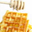 Delicious Belgian waffles and stick to honey isolated on white — Zdjęcie stockowe