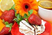 Lemon tea ,lemon,gerbera,cake and strawberries lying on the oran — Stock Photo