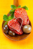 Strawberry, hearts and chocolate candy in the wooden spoon of th — Stock Photo