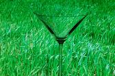 从概念上讲照亮马提尼酒杯在背景上的绿色 — 图库照片