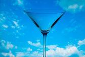 Koncepčně osvětlené skleněné martini proti obloze — Stock fotografie