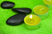 Burning candle and spa black stones lying on the towel — Stock Photo