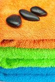 三个多彩色的毛巾和 spa 黑色的背景 — 图库照片