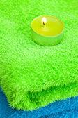 Een brandende kaars liggend op de handdoek — Stockfoto