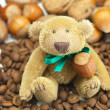Teddy bear with a bow, coffee beans and nuts — Stock Photo #6133582