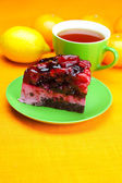 Beautiful cake with berries on a plate and a cup of tea on the o — Stock Photo