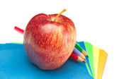 Apple, colored paper and pencils isolated on white — Stock Photo