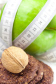 Apple, nuts, cookies and measure tape isolated on white — Stock Photo