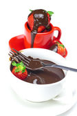 Melted chocolate in a cup, fork and strawberries isolated on whi — Stock Photo
