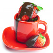Strawberries in chocolate lying in a red cup isolated on white — Stock Photo #6141310