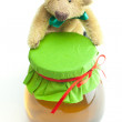 Stock Photo: Teddy bear and jar of honey isolated on white