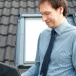 Young man using a laptop against the window and roof — Stock Photo