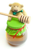Teddy bear ,stick to hohey and jar of honey isolated on white — Stockfoto