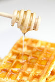 Delicious Belgian waffles and stick to honey isolated on white — Stock Photo