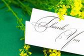 Carte et fleur de champ jaune signent merci sur backgro vert — Photo