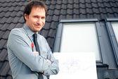 Arquitecto joven presentando un proyecto contra el fondo — Foto de Stock