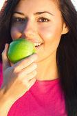 Retrato de una bella mujer joven con manzana al aire libre — Stockfoto