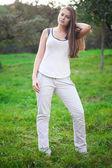 Giovane e bella donna in piedi sull'erba verde — Foto Stock